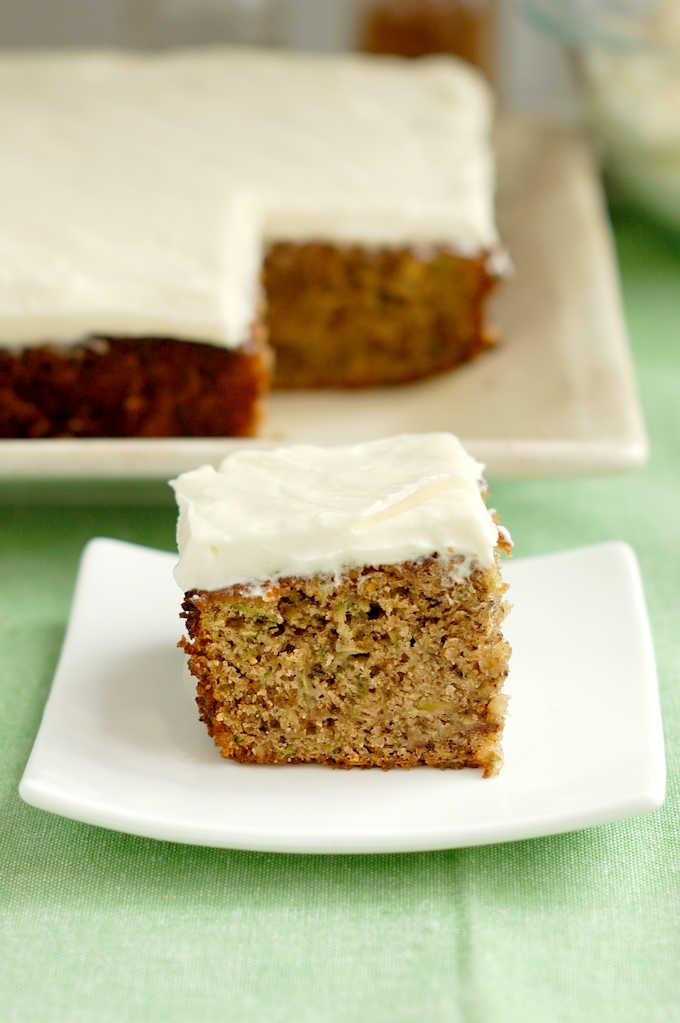 a slice of zucchini cake with cream cheese frosting on a plate
