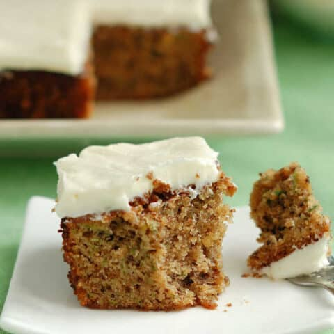 a partially eaten slice of zucchini cake on a plate with a fork