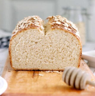 a sliced loaf of honey oatmeal bread on a cutting board