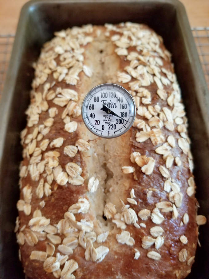 a baked loaf of honey oat bread with a thermometer at 190 degrees F.
