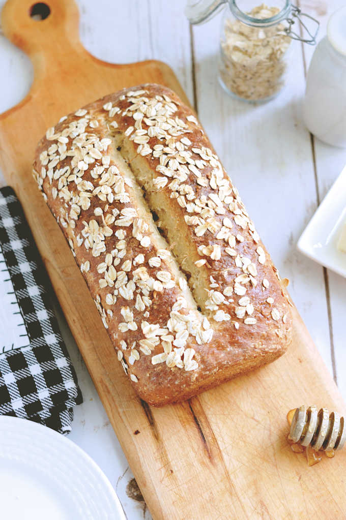 a loaf of honey oatmeal bread on a cutting board