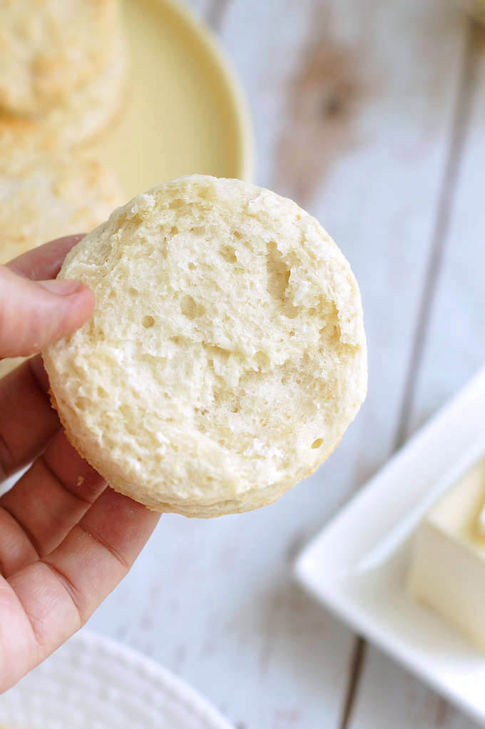 a hand holding half a sourdough biscuit