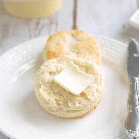 a sourdough biscuit on a plate with a pat of butter