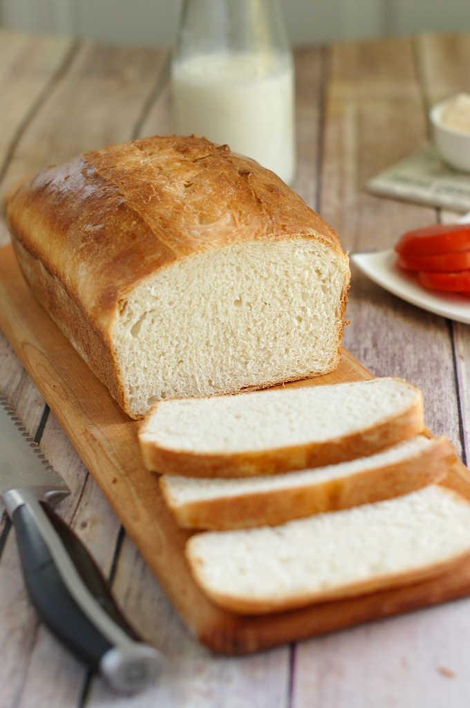 a sliced loaf of sourdough sandwich bread on a cutting board