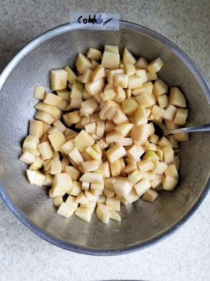 a bowl of chopped apples with sugar and cinnamon