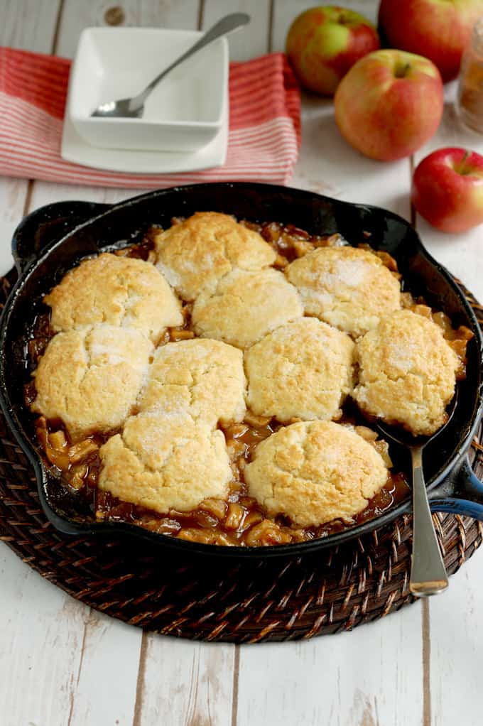 a cast iron skillet with biscuit topped apple cobbler