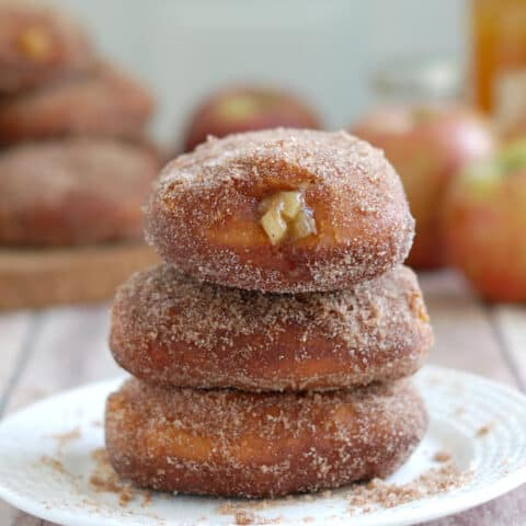 three apple filled cider donuts on a plate