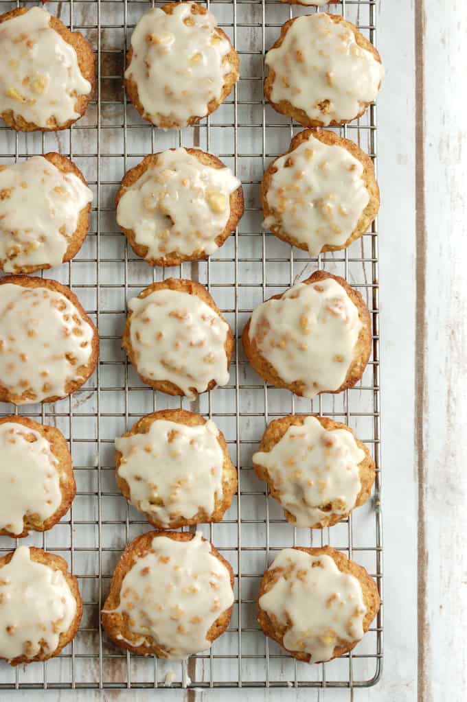rows of iced apple oatmeal cookies on a cooling rack