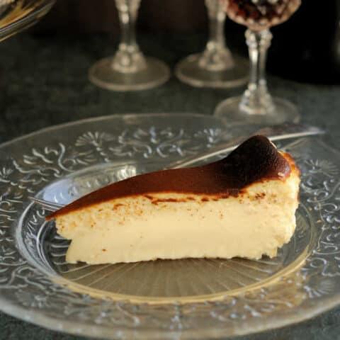 a slice of san sebastian cheesecake on a glass plate