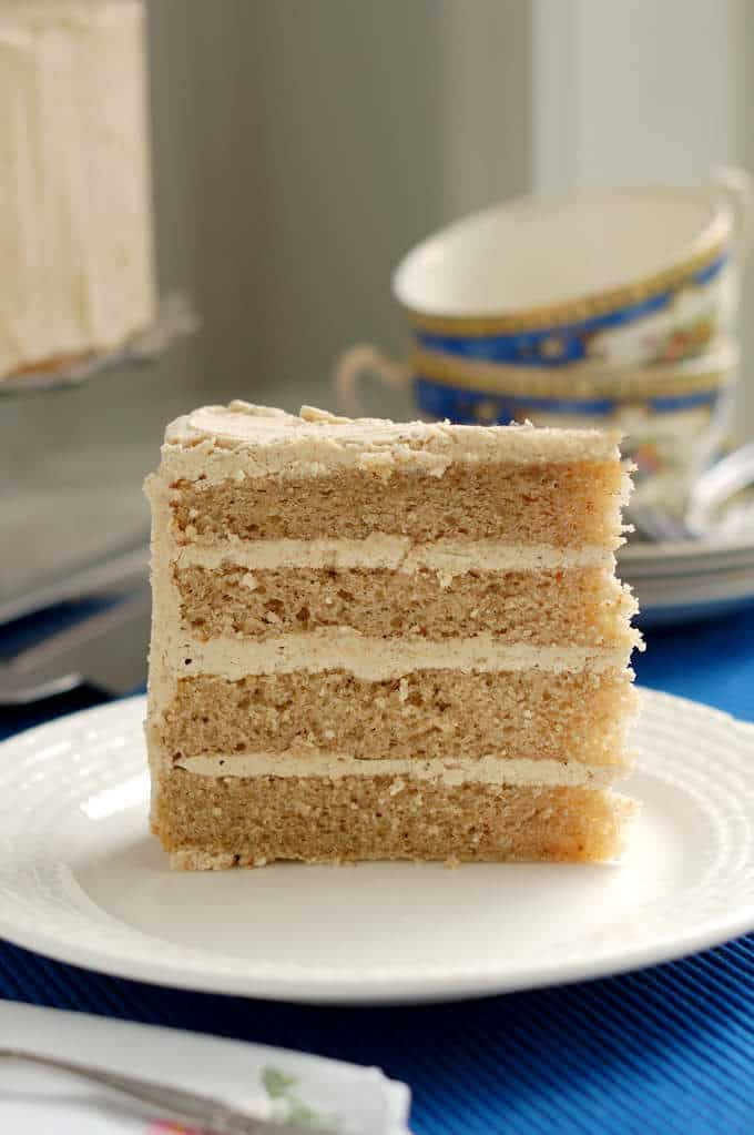 a slice of 4 layer spice cake with spiced ganache on a plate