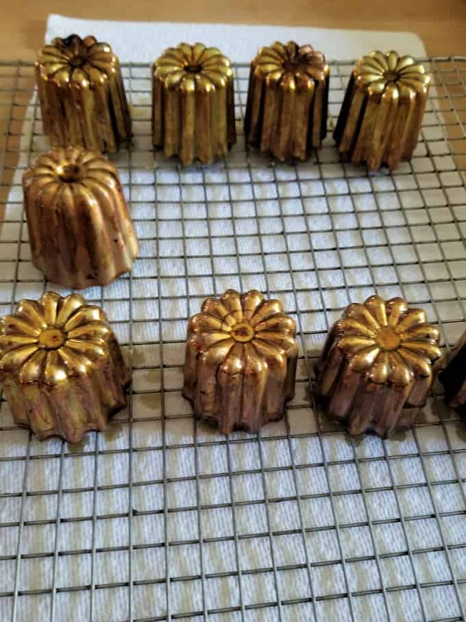 canele molds draining on a baking rack
