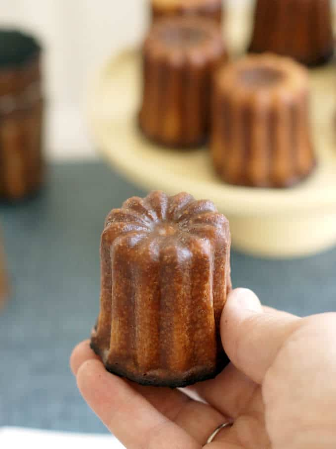 a hand holding a french canele