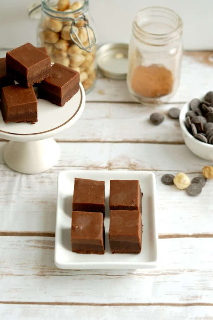 a table with trays of layered hazelnut truffles, a jar of cinnamon and some hazlenuts