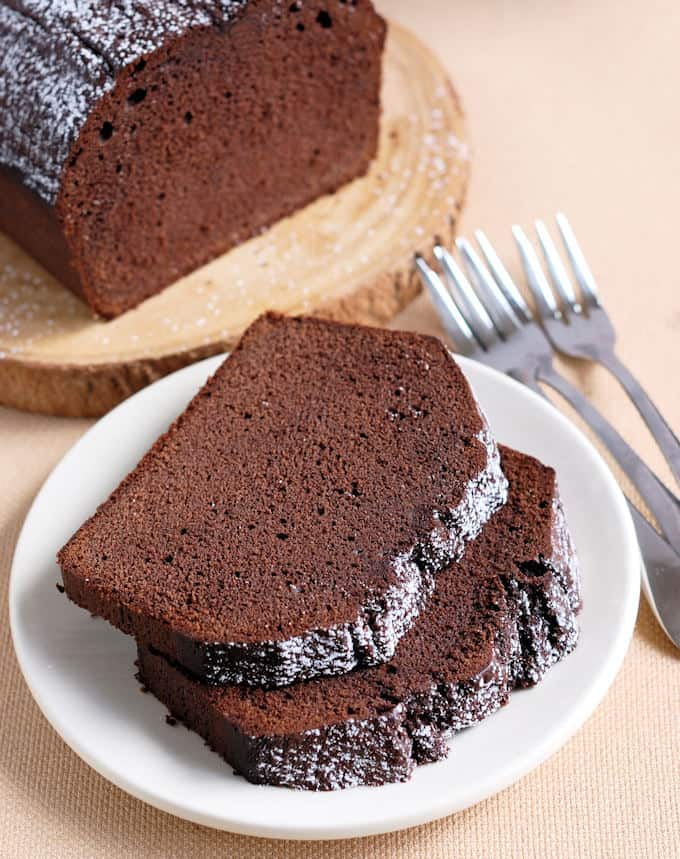 two slices of chocolate pound cake on a white plate.