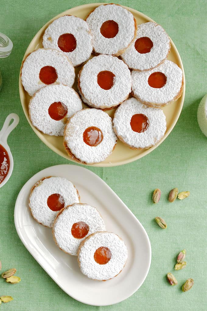 a plate of pistachio apricot linzer cookies in front of a cake stand with more cookies