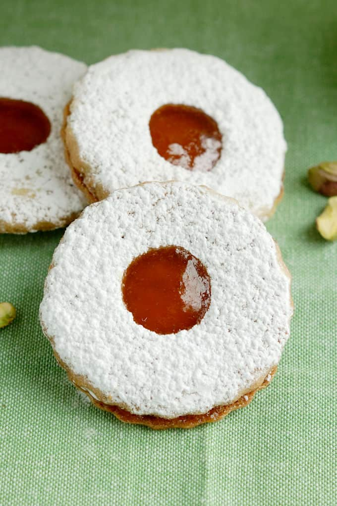 three pistachio linzer cookies on a green background
