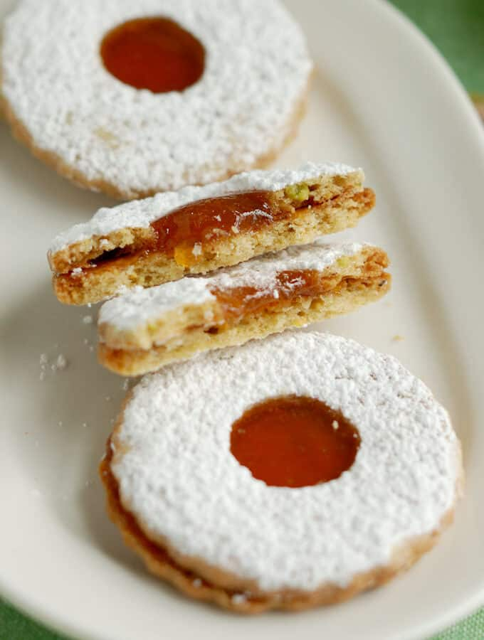 a plate with two whole and one broken pistachio linzer cookie