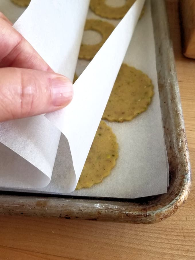 a sheet pan with layers of parchment paper and unbaked pistachio cookies ready for the freezer