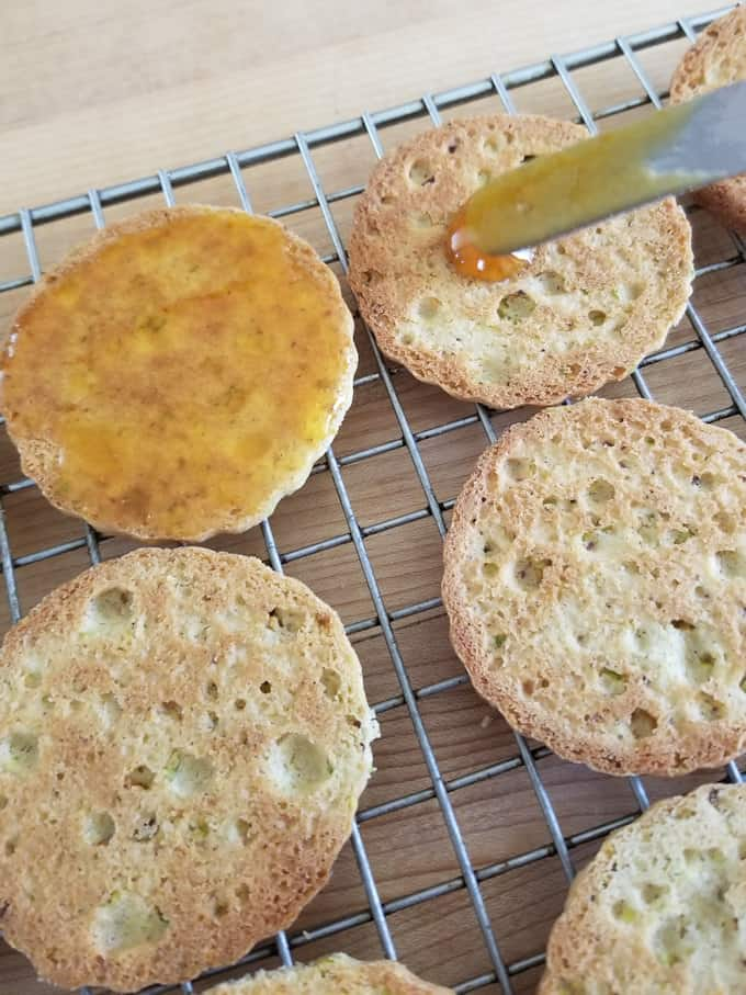 spreading apricot preserves on the flat side of a pistachio cookie