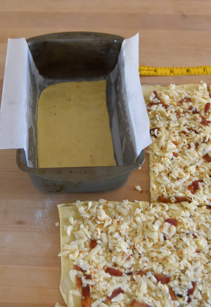 bread dough topped with bacon and pepper jack, ready to layer into a loaf pan.