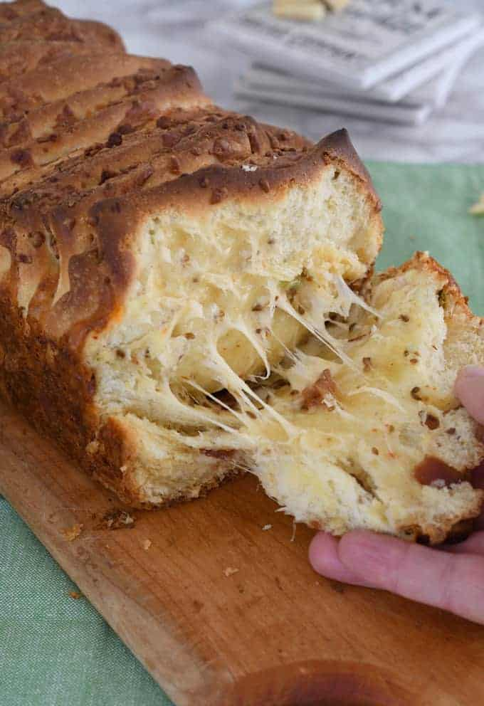 a hand pulling off a slice of bacon and pepper jack pull apart bread