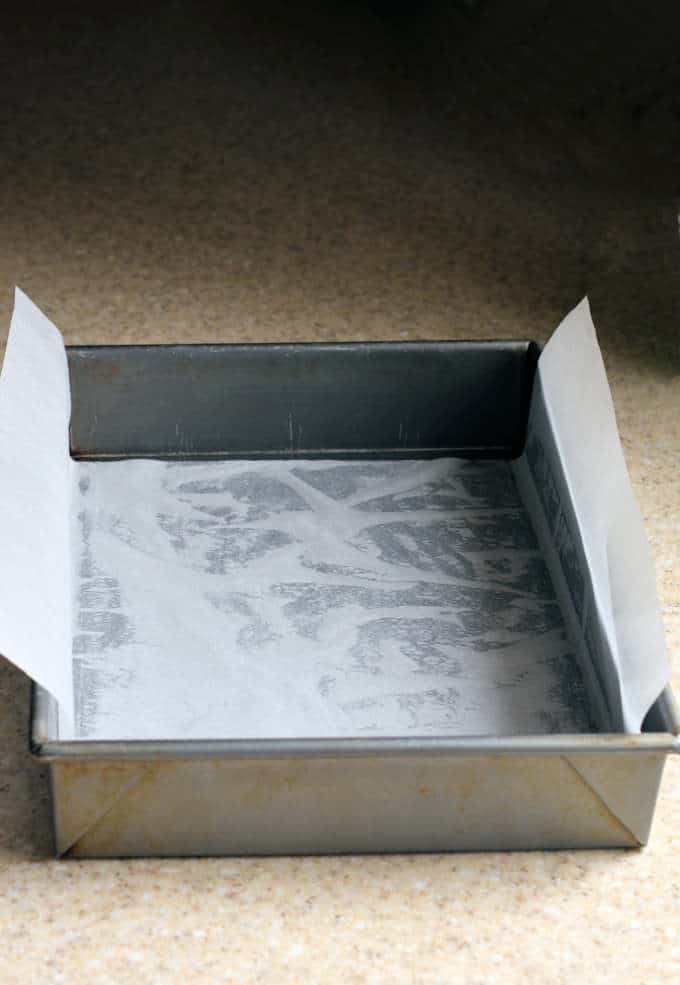 a photo showing how to line a 13x9 baking pan with parchment paper to bake brownies