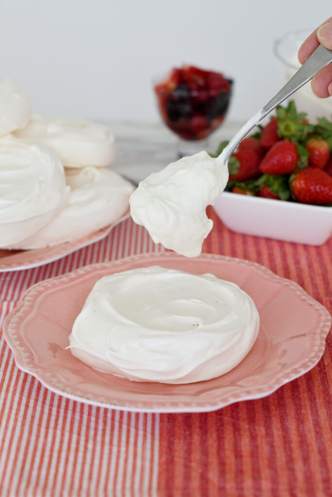 an individual pavlova on a pink plate and a spoon dropping whipped cream