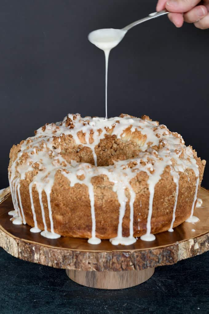 a spoon drizzling icing on a sourdough coffee cake