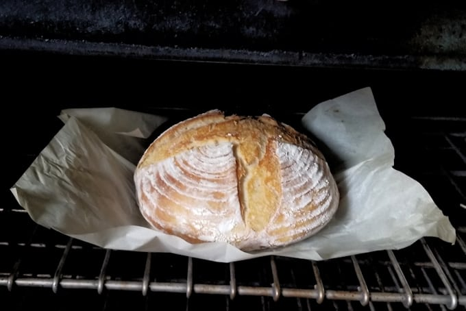a loaf of sourdough bread on a sheet of parchment paper baking directly on the oven rack