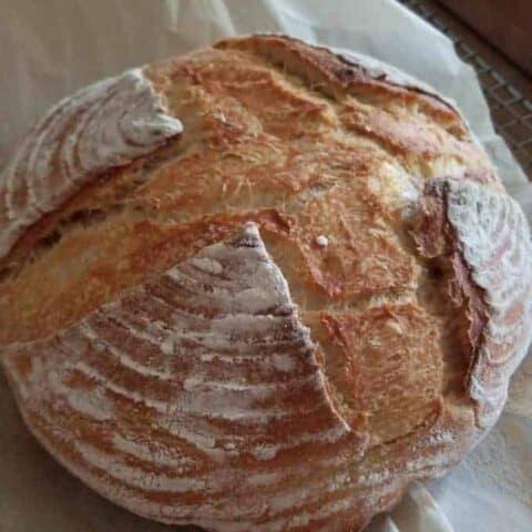 a loaf of sourdough bread on a piece of parchment paper