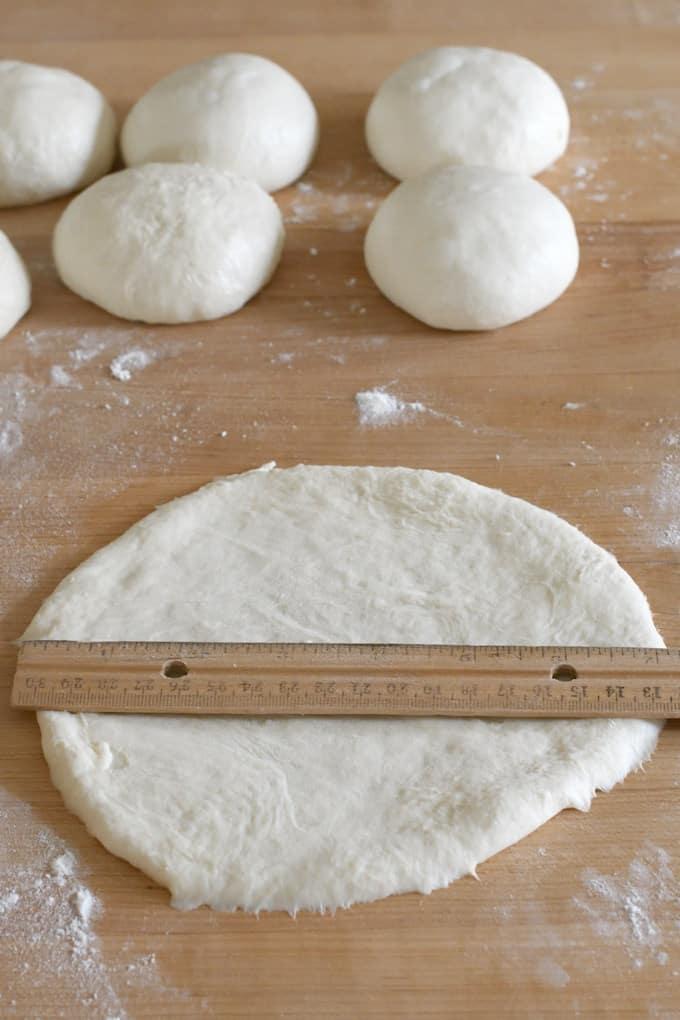 a ruler measuring a round of dough