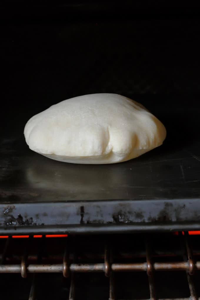 a sourdough pita bread puffing in the oven