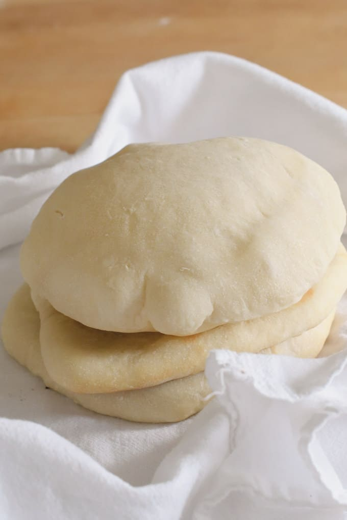 a stack of warm sourdough pita bread wrapped in a kitchen towel