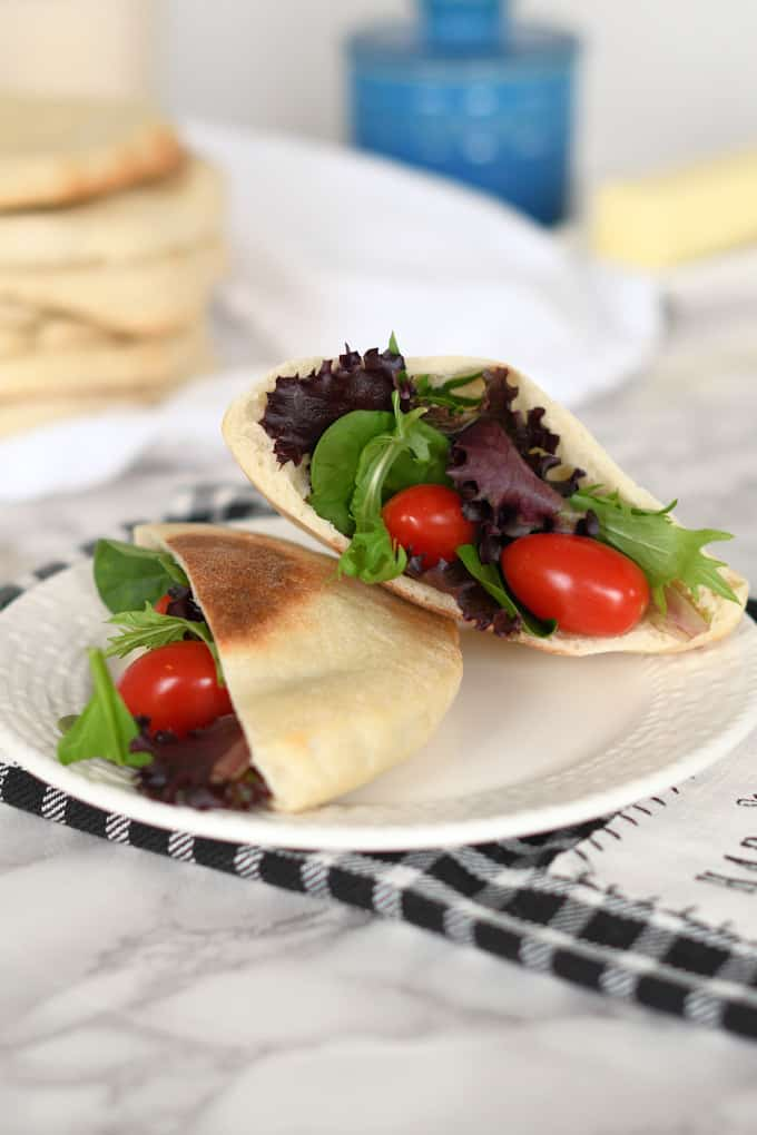 a plate with a sourdough pita bread filled with salad