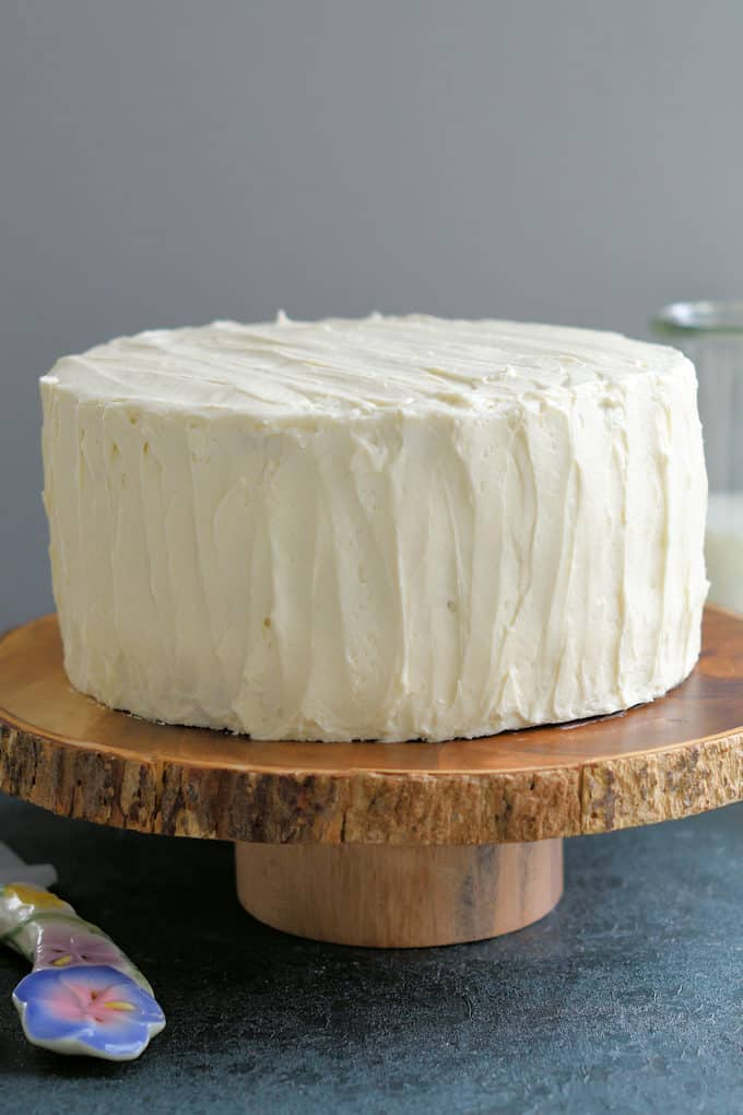 a vanilla iced cake on a cake stand
