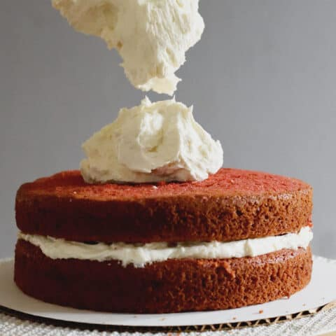 a spatula dropping ermine frosting onto a red velvet cake