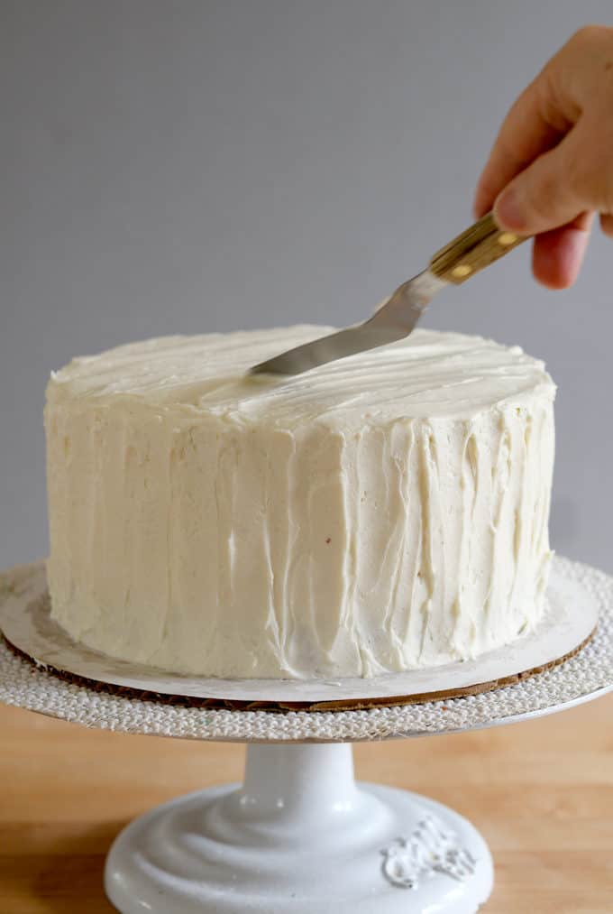 a small spatula icing a cake with ermine frosting