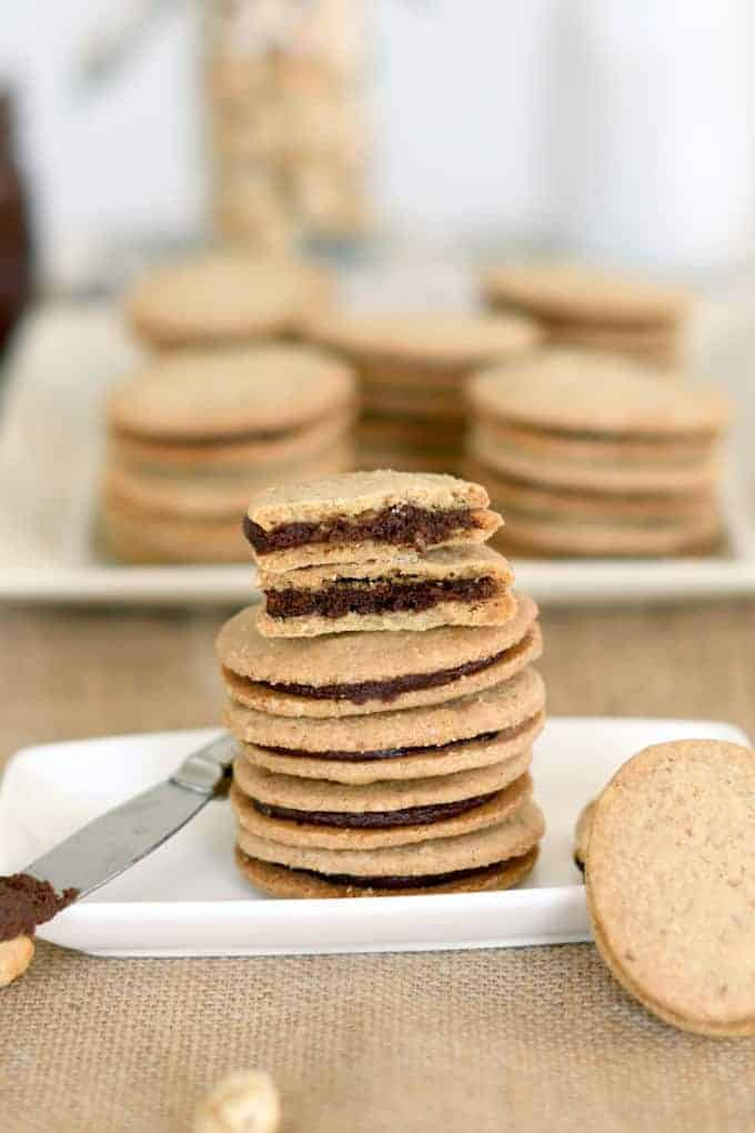 a stack of nutella sandwich cookies with one broken in half to show the filling