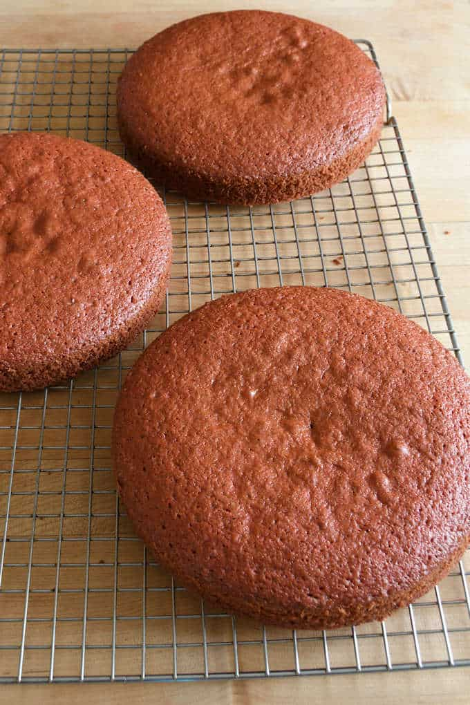 three layers of red velvet cake cooling on a rack
