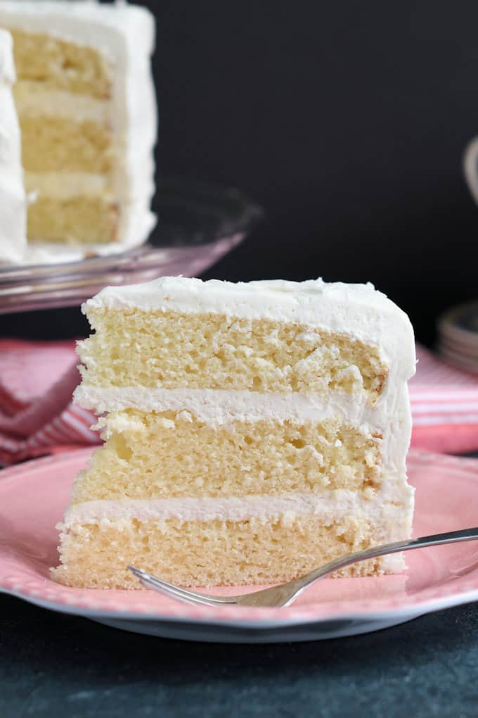 a slice of vanilla buttermilk layer cake on a pink plate