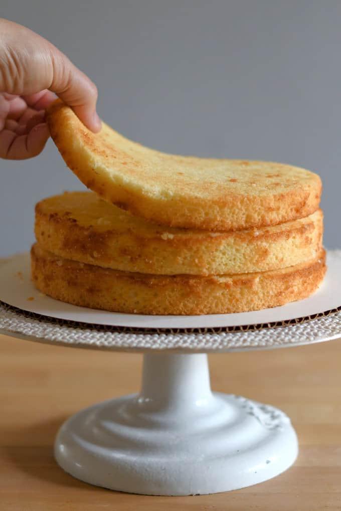 three vanilla buttermilk cake layers on a cake stand