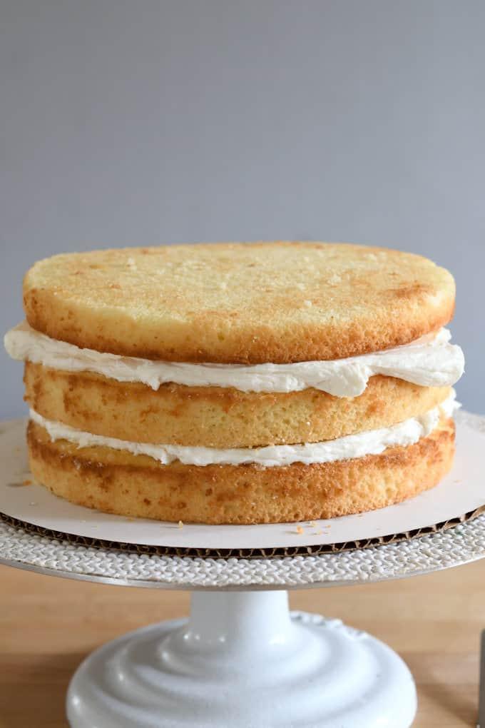 an uniced vanilla buttermilk cake on a cake stand