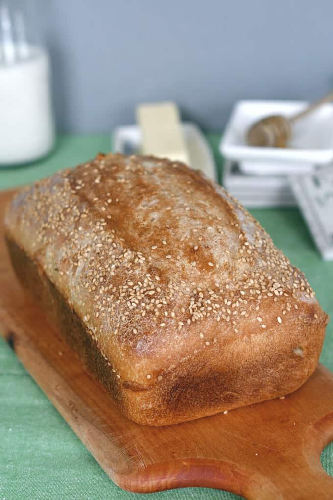a freshly baked loaf of sourdough whole wheat sandwich bread on a cutting board