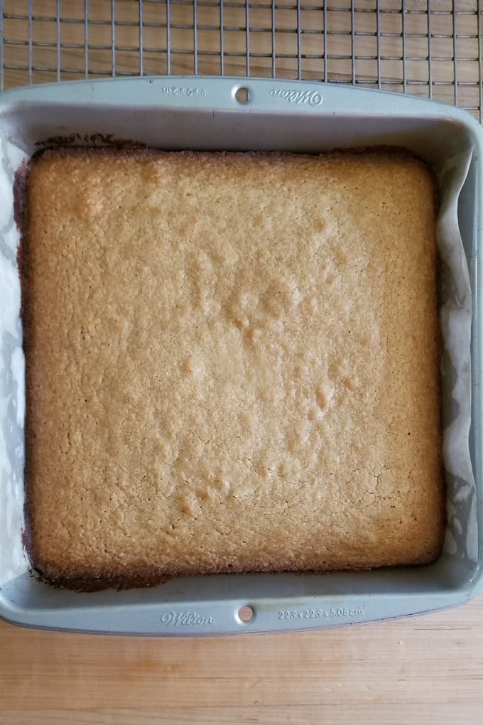 baked blondies in a pan on a cooling rack