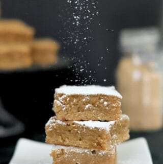 three blondies on a plate sprinkled with powdered sugar