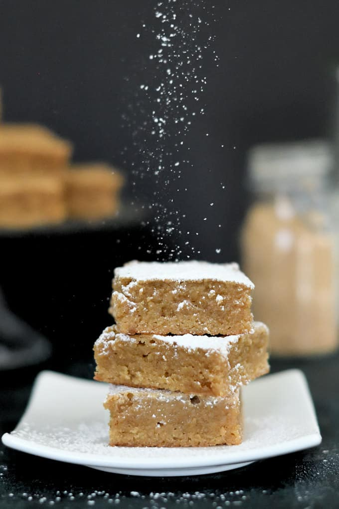 a stack of three blondies being sprinkled with powdered sugar