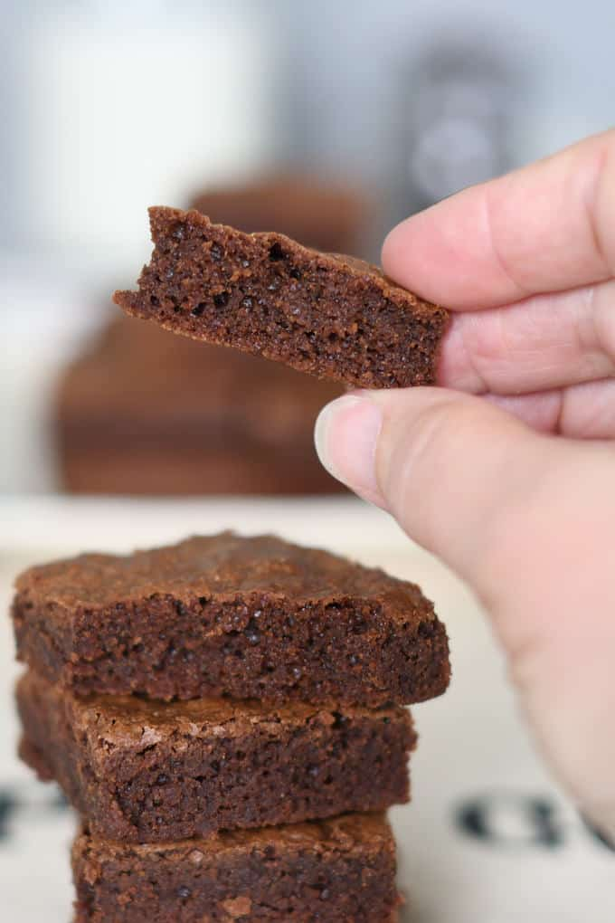 a hand holding a piece of a fudgy brownie