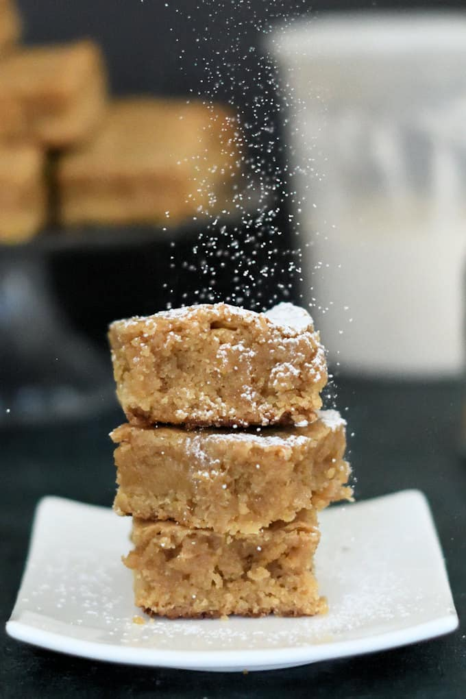 three butterscotch blondies on a plate sprinkled with sugar