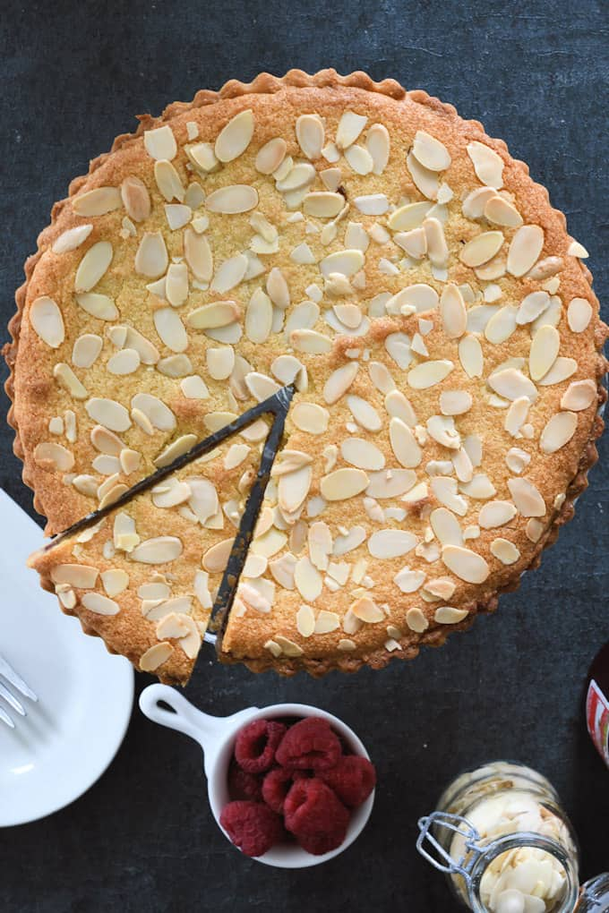 a top view of a bakewell tart with one slice cut