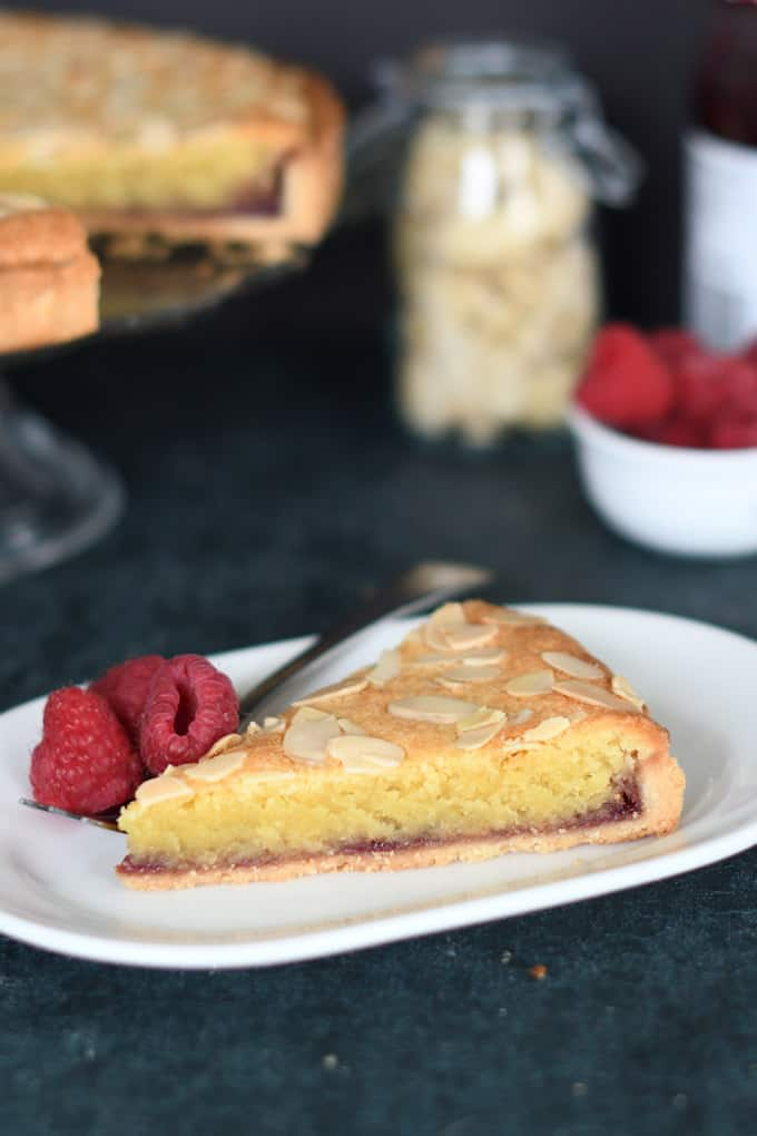 a slice of bakewell tart on a white plate with raspberries